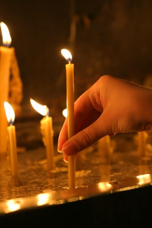 christian candle: woman hand lighting candles  in a church