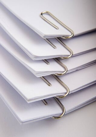 office appliances: close up of paperclips holding paper sheets on white background Stock Photo