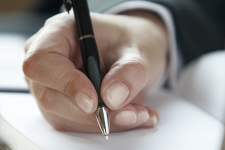 hand holding pen: close up of business woman hand holding pen and writing in notebook Stock Photo