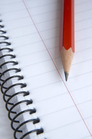 lined up: close up of wire bound notebook and pencil