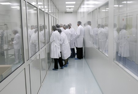 healthcare visitor: visitors in white coats in interior of a pharmaceutical industry Stock Photo