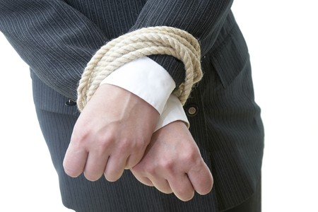 close up of businesswoman hands tied with rope