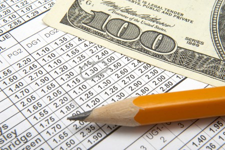 betting: close up of sports betting slip, pencil and one hundred dollars