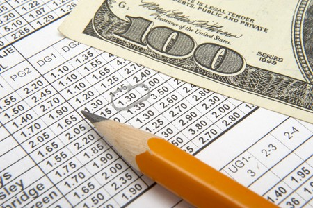 one hundred dollars: close up of sports betting slip, pencil and one hundred dollars