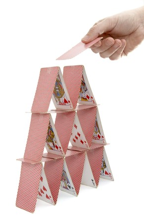 build up: close up of house of playing cards and hand on white background with path