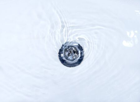 the draining: close up of drain and water in bathroom Stock Photo