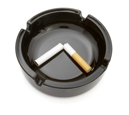 quiting: close up of ashtray and cigarette on white background Stock Photo