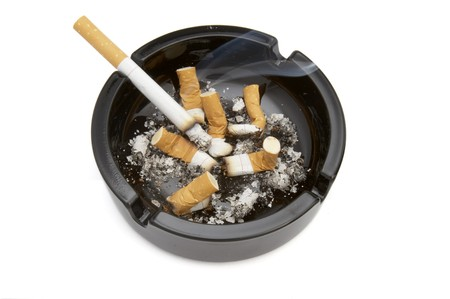 quiting smoking: close up of ashtray and cigarettes on white background