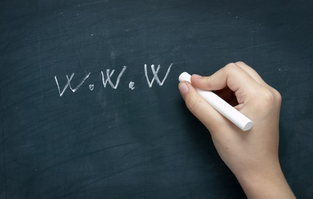 writing utensil: close up of hand writing web lwtters on blackboard  Stock Photo
