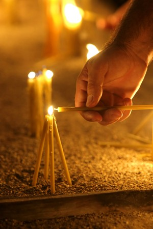 burning man: man hand lighting candles  in a church Stock Photo
