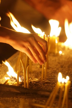 enlightening: woman hand lighting candles  in a church