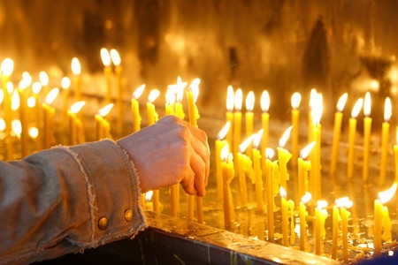 devout: man hand lighting candles  in a church Stock Photo