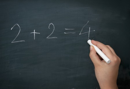 close up of hand writing numbers on blackboard  photo