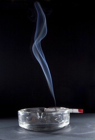 stopping: close up of ashtray and burning cigarette with smoke Stock Photo