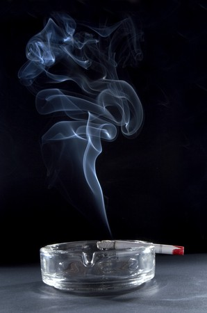 quiting smoking: close up of ashtray and burning cigarette with smoke Stock Photo
