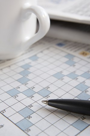 stimulate: close up of empty crosswords and pen