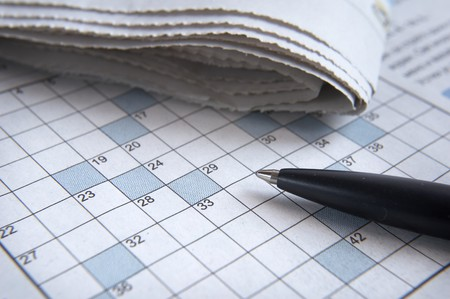 figuring: close up of empty crosswords and pen