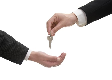 close up of two businesspeople giving keys on white background with path photo