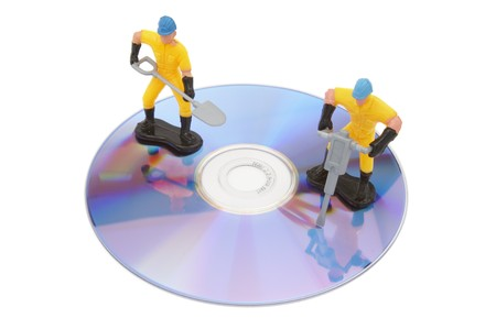 close up of cd failure and toy workers on white background with path photo