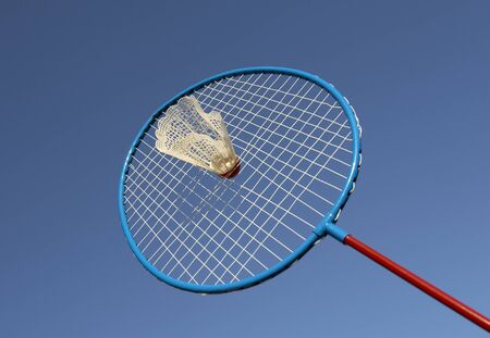 hunted: close up of badminton racquet and shuttlecock with blue sky background