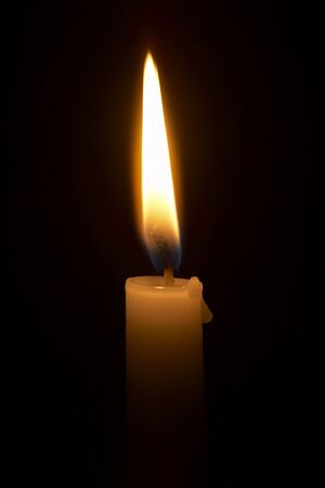 close up of lighted candle on black background  photo