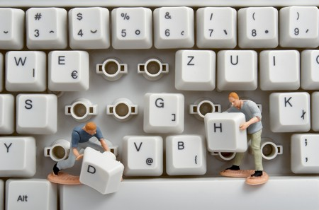 restoring: close up of computer keyboard and toy workers