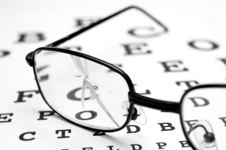 close up eyes: close up of broken glasses and snellen chart Stock Photo