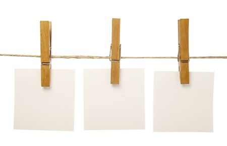 board pin: close up of postit reminders and clothespins attached to a rope on white background