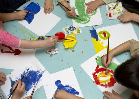 writing activity: little children painting during art class