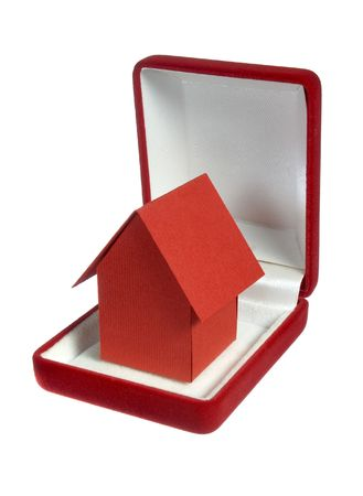 close up of miniature house in wedding rings box on white background