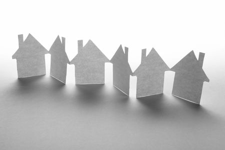 row of houses: close up of houses cut out of paper on white background