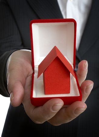 close up of businesswoman and miniature house in wedding rings box photo