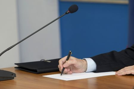 spokesman: close up of conference meeting microphones and businessman writing