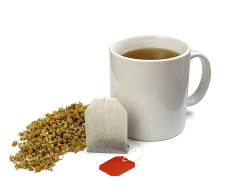 close up of tea bag, chamomile plant and coffee cup on white background with clipping , shadow is not included photo