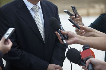correspondent: close up of conference meeting microphones and businessman