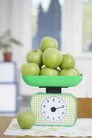 closeup of green apples on kitchen scale photo