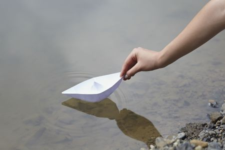 childish: close up ofhand and paper boat in river Stock Photo