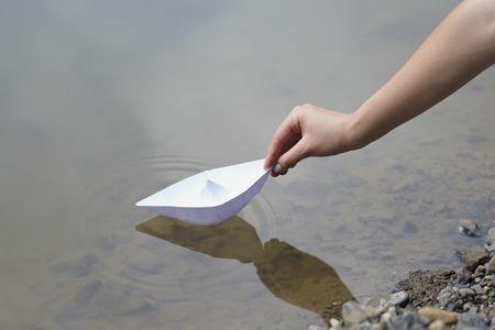 the boat on the river: Close up ofhand y el papel de barco en el r�o