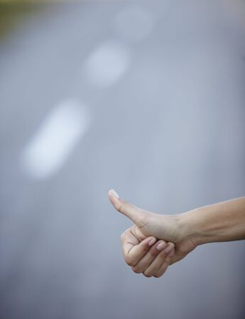 girl hand hitchhike on empty road photo