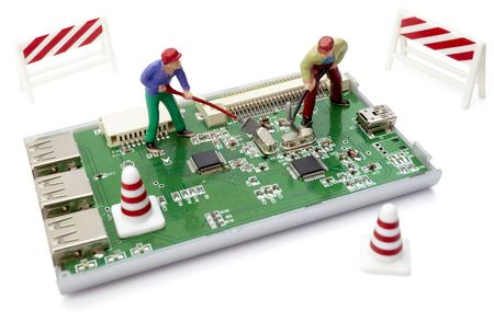 electronic circuit: miniature toy workers repairing computer part with circuit