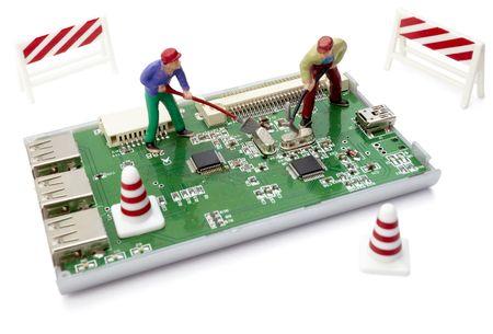circuitos electronicos: trabajadores de juguete de miniatura reparaci�n de parte de la computadora con circuito Foto de archivo