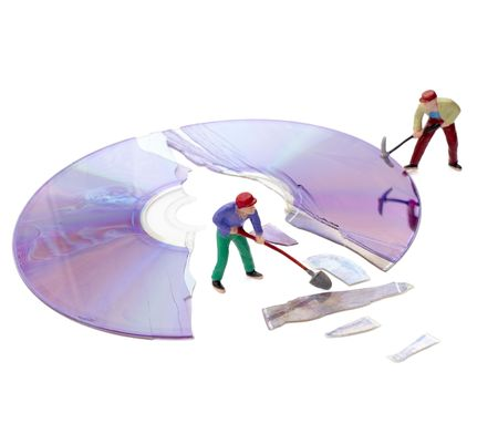 compact disk: miniature toy workers repairing broken compact disk Stock Photo