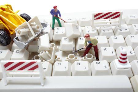 miniature toy workers repairing computer keyboard photo