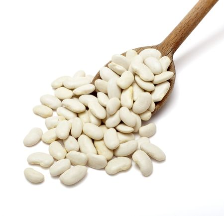 haricot: close up of raw haricot beans in wooden spoon on white background