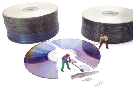 refurbish: miniature toy workers repairing broken compact disk Stock Photo