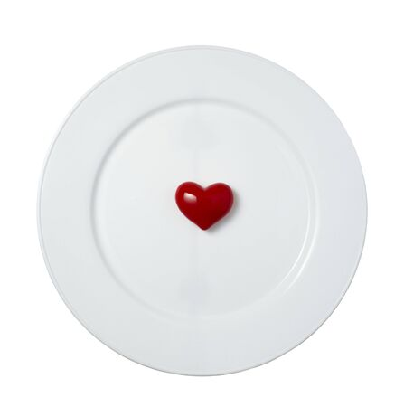 shaped: close up of red heart shape object on white plate  on white background