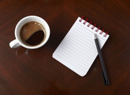 close up of coffee cup and notebook with pencil on table photo