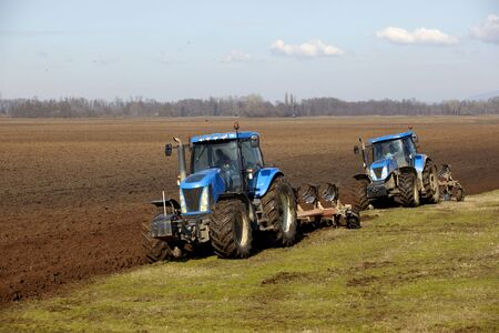 tractor working on cultivated land cultivation  photo