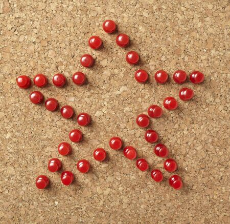 chipboard: close up of red starshape of push pins on cork board