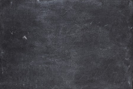 an elementary: close up of a black dirty chalkboard
